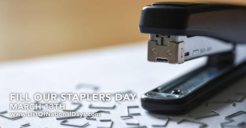 A black stapler with staples sprinkled around it.