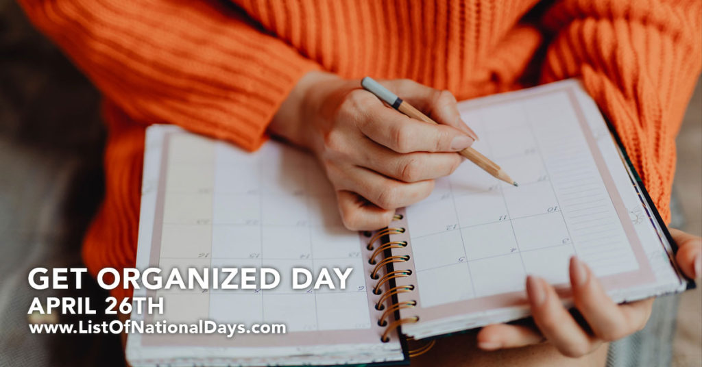 A woman in an orange sweater writing in her planner.