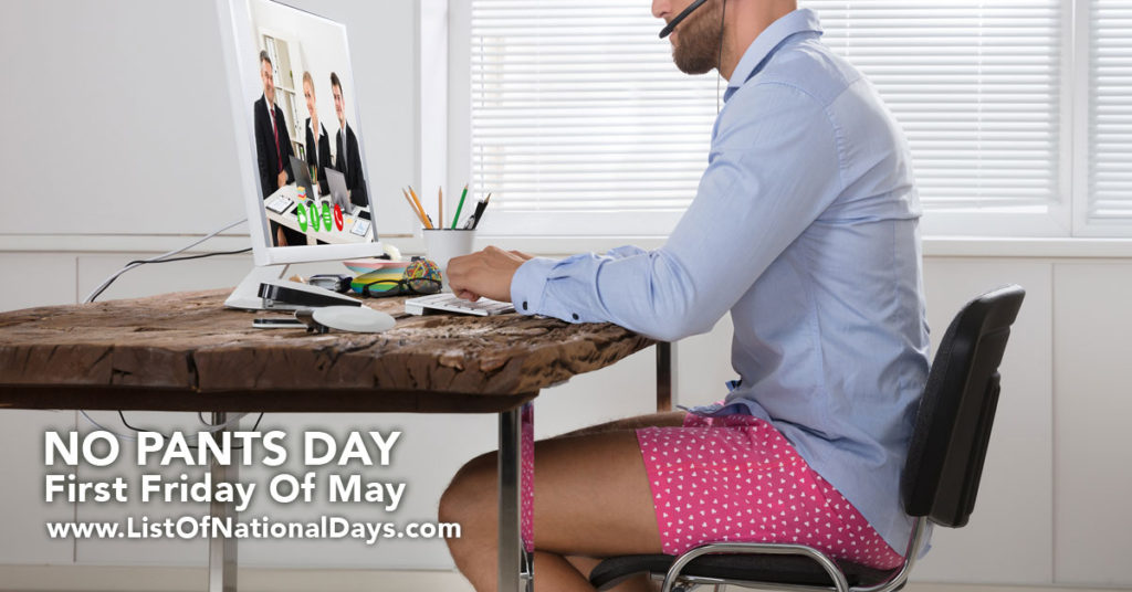 A man sitting at his desk in pink boxer underwear.
