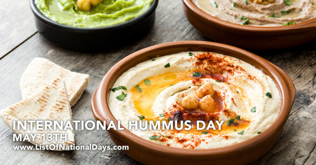 A bowl of hummus with a stack of pita bread.