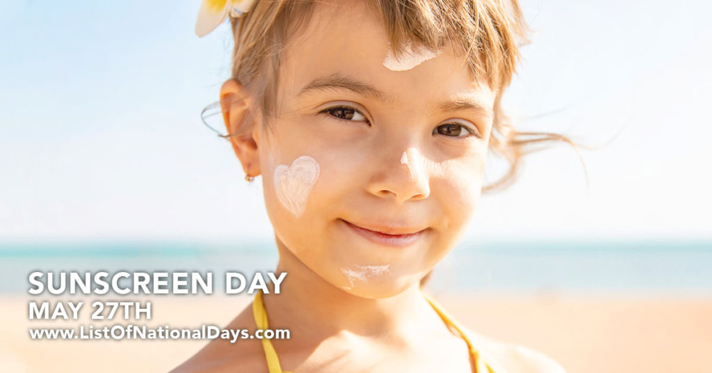 A young girl smiling with a heart one her check made out of sunscreen.