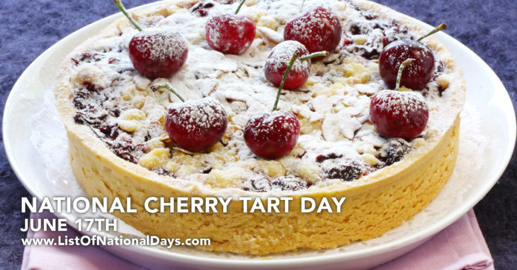 A delicious looking cherry pie with whole cherry's on the top covered in powdered sugar.
