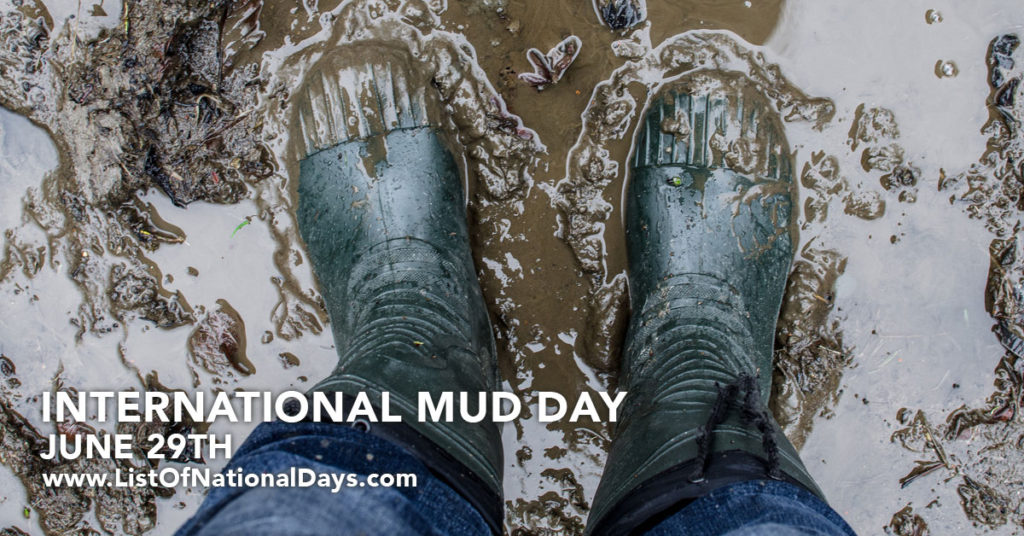 black rain boots standing in a puddle of mud on a rainy day.