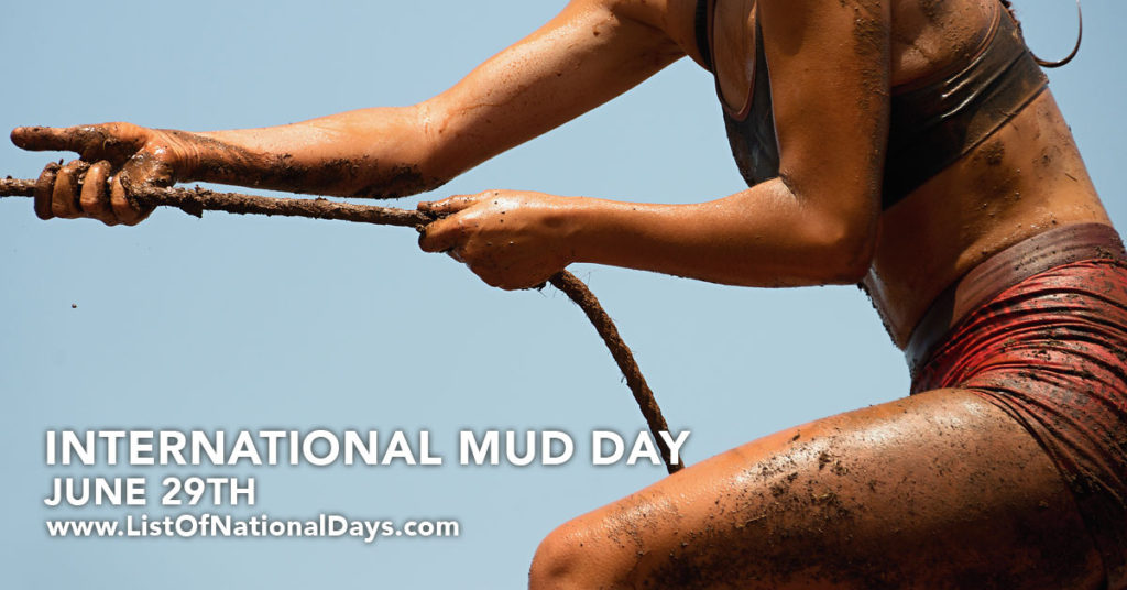 A fit woman pulling her self up  with a muddy rope in a mud run.