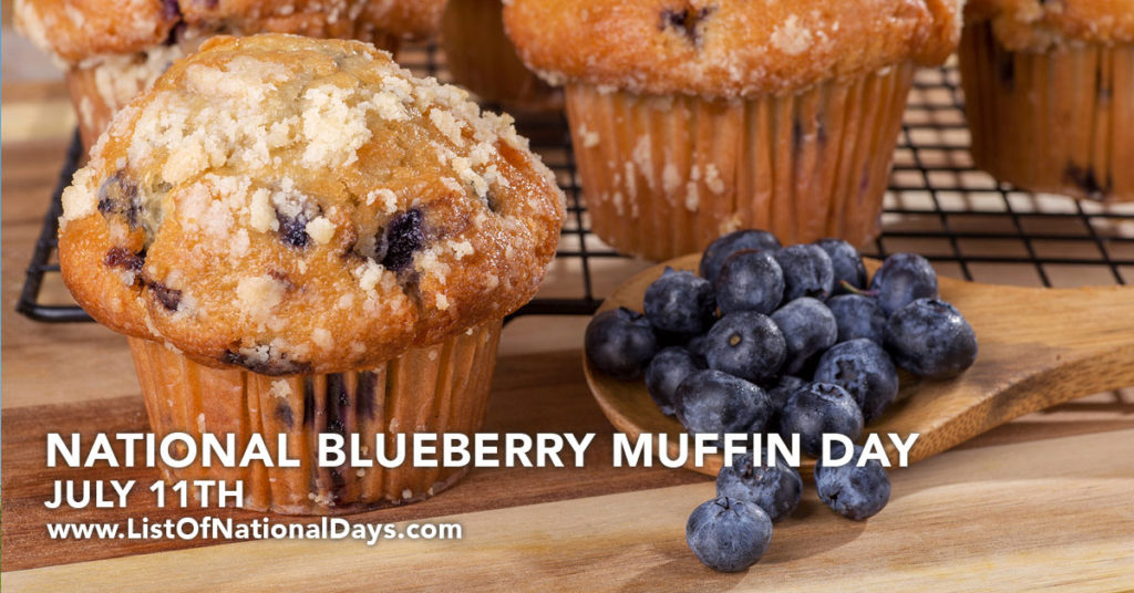 a wooden spoon full of blueberries in front of a rack of blueberry muffins.